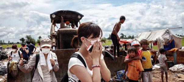 Una turista japonesa se tapa la boca y la nariz ante el fuerte olor que desprenden los gases del basurero de Siem Reap. Esta turista visita el basurero dentro de una ruta turística.